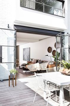 Black steel-frame bifold doors, pale grey timber decking, white wire outdoor chairs