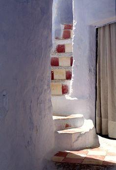 Escala blanca I vermelle, quasi secreta, amagada entre parets blaves