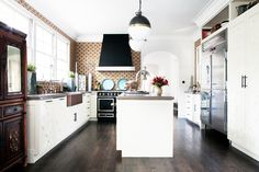 Kitchen with dark wood floors, white cabinets, statement light fixtures, stainless steel fridge, large windows, white walls and patterned wallpaper