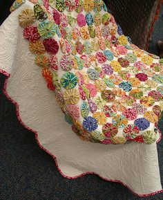Store bought quilt, yoyo's appliqued on and then new binding applied. Beautiful!