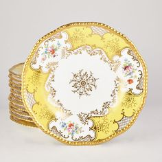 Coalport Gilt Decorated Porcelain Dessert Plates  Retailed by Gilman Collamore, Fifth Avenue, New York  Each foliate decorated white center continuing to a yellow and white rocaille border with floral reserves, irregular rim.