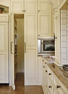 """While panels alongside the refrigerator blend in with surrounding cabinets, they are actually doors opening to a hidden walk-in pantry."""