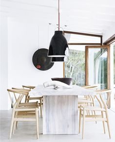 The chairs  are the Wishbone chairs from Wegner. The black Carvaggio pendants are from Danish designer Cecilie Manz
