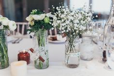 Glass jars wrapped in ribbon and filled with white flower stems including gypsophila - Image by Ross Hurley Photography - Winter white wedding in a rustic barn with bespoke lace wedding dress, grey Debenhams Bridesmaid gowns & herringbone Grooms suit with turquoise lining & bow tie.