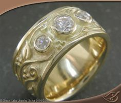 This ring is 18kt yellow gold with a carved vine pattern. It is ~8mm wide. It is set with (3) round diamonds totaling ~.22ctw.