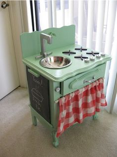 Homemade cute!  Just a night stand, a mixing bowl, an old faucet, wood stove knobs and of course a cabinet curtain to make a play kitchen.