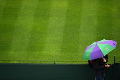 A fan with an umbrella at Wimbledon on Day Six