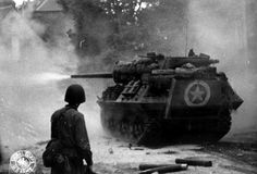 A GI watched an M10 tank destroyer do its work in Saint-Lô