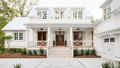 dormers over a welcoming front porch w/ 3 French doors