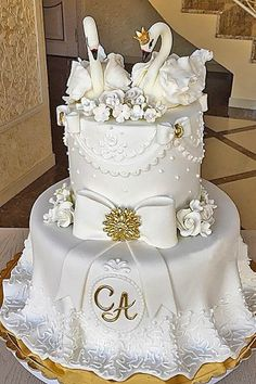 white and gold cake with swan topper