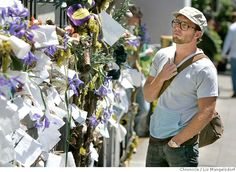 Timo Weiland of Stockholm, Sweden, surveys the AIDS remembrance wall at the corner of Castro and 18th streets in San Francisco on Monday. The wall marking 25 years of the AIDS epidemic features messages and iris flowers, which are displayed throughout the Castro neighborhood.