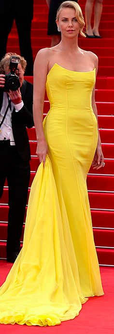 Charlize Theron shines out at Cannes in skintight yellow gown by Dior and amzing Chopard earrings as she joins stars at Max Max premiere.