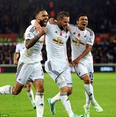 Sigurdsson is congratulated by Kyle Bartley (left) and Montero (right) after his equalising goal as they go on to beat Arsenal 2-1 at the Liberty
