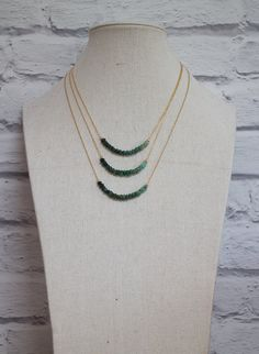Row of raw, hand cut, rustic Emerald Beads have been strung to create a beautiful ombre effect from the darkest green to pale mint, set seamlessly in the centre of a 14K Gold Fill rolo chain. Also available in 925 Sterling Silver too.  Perfect for a May Birthday! Great for layering too!  New more refined version with faceted beads http://etsy.me/2eig3Wx  •Natural Emerald beads are 4.5-5mm approx. •14K gold fill rolo chain and beads. Finished with a spring clasp closure in the chosen metal…