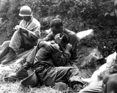 An American soldier comforts a fellow infantryman whose close friend has been killed in action, Haktong-ni area, Korea, August 1950. A corpsman fills out casualty tags in the background.