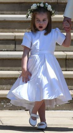 Princess Charlotte of Cambridge in a pretty white frock by Clare Waight Keller for Givenchy couture bridesmaid dress. It was made of ivory silk radzimir, and were high-waisted with short puff sleeves, pockets and pleated skirt, hand finished with a double silk ribbon detail tied at the back in a bow and a pretty floral crown which replicated the flowers used in the bridal bouquet. Teamed with a pair of white leather Aquazurra shoes, each monogrammed with the bridesmaid's initials, and the…