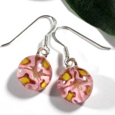 These pretty pink millefiori earrings will adorn your ears with a bouquet of flowers.  The earrings are a round shape and have four pink flowers with yellow centers. They are made from slices of mille
