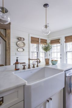 Farmhouse Kitchen - beautiful marble countertops, a farmhouse sink and vintage looking sink faucet are surrounded by shiplap walls. This amazing kitchen was found on Instagram @anisadarnell from Truth and Co. - via Nina Hendrick