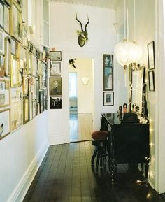 High ceilings,frames, white walls, antlers, lights and dark floors.