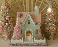 This pretty Putz style Christmas house resembles a scene from a fairytale! It is painted in soft aqua with a pink roof and silver trim. Aqua walls