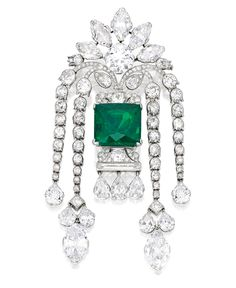 PLATINUM, EMERALD AND DIAMOND BROOCH.     Centered by a modified emerald-cut emerald topped by a round diamond, framed by five marquise-shaped diamonds, suspending four undulating fringes set with two marquise-shaped diamonds and nine pear-shaped diamonds accented throughout with old European, single-cut, pear-shaped and baguette diamonds; circa 1920.