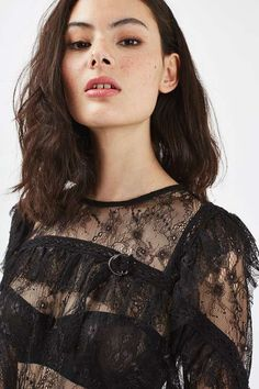 Sheer tops are a party staple for now. This long sleeve style is finished in delicate lace with feminine ruffles. We love the ultra-modern d-ring detail to the chest for an added edge. We've styled with a lace pencil skirt for a chic going-out look. #Topshop