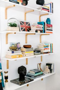 """Lucy's Apartment Makeover - """"I'm a big believer that bookshelves are for books... And I like to keep similar books together. You can either organize by subject or loosely group them by color, so it doesn't feel like too much of a hodgepodge. If you place the books in groups, your eye has a place to land, and then move on. Once the books are in, you can stack some horizontally, so they act like bookends. Finally, layer some other pieces in, but be careful not to overstuff shelves. You want it…"""