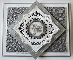 cut the Diamond Squares Background out of silver card, then used the Double Pierced Squares to cut it into a frame.  I added a small raised frame cut from the same die set.  Next I cut the Sophia die in white which fit over the frame white Double Stitched Octagons