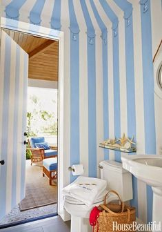 Blue and white stripes are painted for a faux tenting effect in this bathroom off of the back porch in a Palm Beach home.