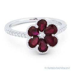 The featured ring is cast in 18k white gold and showcases a centerpiece flower design adorned with a round cut diamond centerstone, pear-shaped ruby petals, and round cut diamond accents set halfway along the band.