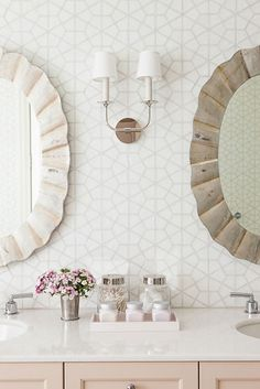 Powder room with hexagon print wallpaper, twin mirrors, marble countertops and pale pink cabinets | Caitlin Moran Interiors