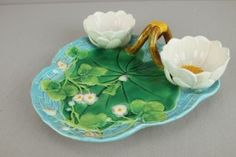 "GEORGE JONES majolica strawberry server with two lily flowers which form cream and sugar over turquoise basketweave tray with vine handle and floral and leaf decor, nice color, hairline, 10 1/2""w"