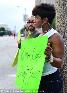 Opposition: The demonstration on Sunday attracted more protesters who set up camp across the street to rally in favor of victim Michael Brown