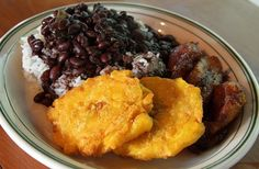 Typical Cuban food..arroz blanco, frijoles negros, masas de puerco y tostones/ black beans & rice with pork and fried green plantains.