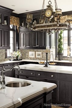 lovely kitchen with dark cabinets and marble countertops