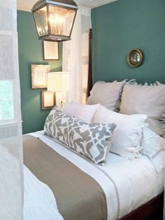 Neutral bedding tones and teal walls. Love the lighting fixture.