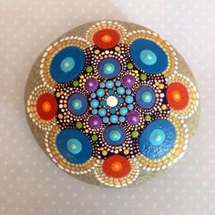 This colourful stone was selected from the rocky shore along Lawrencetown beach, Nova Scotia. The stone has been hand-painted using colours of blue, turquoise, orange and purple; it has been transformed into a mandala stone treasure. The acrylic paint has been sealed with 3+ coats of acrylic protective spray finish. The stone itself is slightly oval and medium-large in size--measuring approximately 8cm x 7cm and 3.5cm thick. It weighs 308g unpackaged. For shipping the stone will be securely…