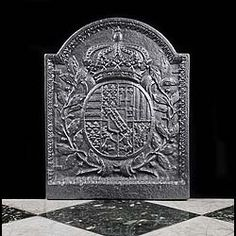 AN ARCHED 19th CENTURY CAST IRON FIREBACK displaying a heraldic coat of arms featuring the fleur de lys of Florence and the bundle of sticks concealing a weapon..being the historic emblem of resistance in an Italian context....and later that used by Mussolini's Fascists.
