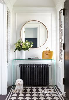 In the foyer, a modern glass waterfall console is an unexpected accent overtop of the original radiator. Home Design, Modern House Design, Interior Design Inspiration, Decor Interior Design, Interior Decorating, Decorating Ideas, Modern Entryway, Entryway Decor, Entryway Mirror