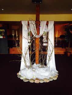 Easter: nice use of cross, branches, rocks and flowing material. Incorporating real plants would bring it more to life.