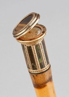 A GOLD MOUNTED WATCH CANE The hinged grip opening to reveal a watch 'BUCHERER'. The handle mounted with a tiger eye and opal. Bearing spurio...