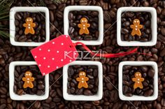polka dots tag with christmas cookies and coffee beans. - Overhead image of coffee beans and Christmas gingerbread cookies inside coffee cups while pink tag with polka dots on top it.