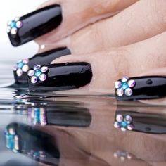 Encantadora manicura de uñas en color negro brillante adornadas con perlas cristalinas y azul cielo brillante formando una flor en las puntas.