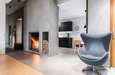 Näyttävä betoninen takka toimii tilanjakajana keittiön ja olohuoneen välillä luo kotiin lämmintä tunnelmaa.