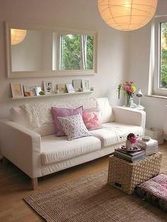 sala de estar decorada com sofá branco, prateleira em cinam do sofá com pequenos quadros, e espelho em cima dea prateleira