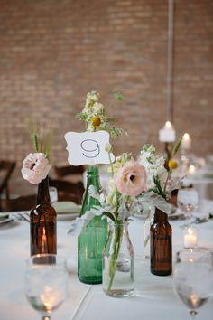 vintage bottles with single stem florals for table decor taken by Megan Saul Photography http://megansaul.com/