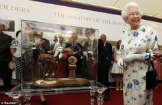 Queen Elizabeth smiles after a member of the Royal Warrant Holders Association unveiled a figure of Zara Phillips riding her horse, Toytown,...