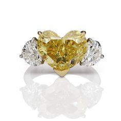 A 7+ carat Fancy Intense Yellow heart shaped diamond flanked by 2 colorless heart shaped diamonds, all set in platinum -the heart is our truest expression of love!