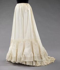 """According to the famous Heather McNaughton of Truly Victorian patterns, typical late Victorian and Edwardian era petticoats similar to this one  """"were made with lots of varied ruffles to them, so you would have 3-4 layers at the hem line in one petti. Start with a full length petti, and put a 6"""" ruffle at the hem. Over that you have a tall ruffle coming off at knee height that goes to the hem, with a 6"""" ruffle on the bottom if it.""""  [Cotton petticoat, Met Museum, c. 1895]"""