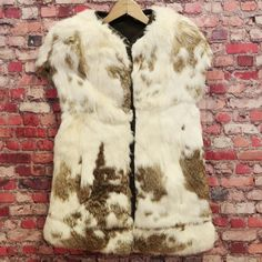 "Rabbit Fur Vest. The vest is in very good condition. Shoulder to Collar: 8"". Arm Hole: 9"". Features a white with brown coloring. Length: 26 1/2"". Listed By: SJ. 